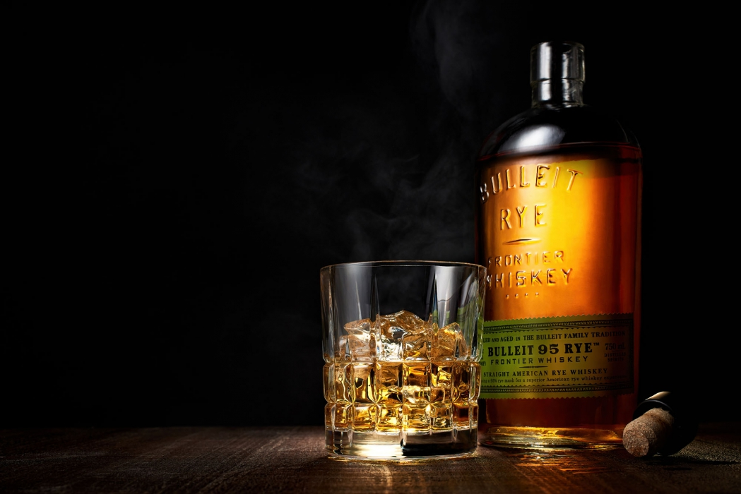 Bullet rye whiskey on a table with glass served neat - drink liquor photography