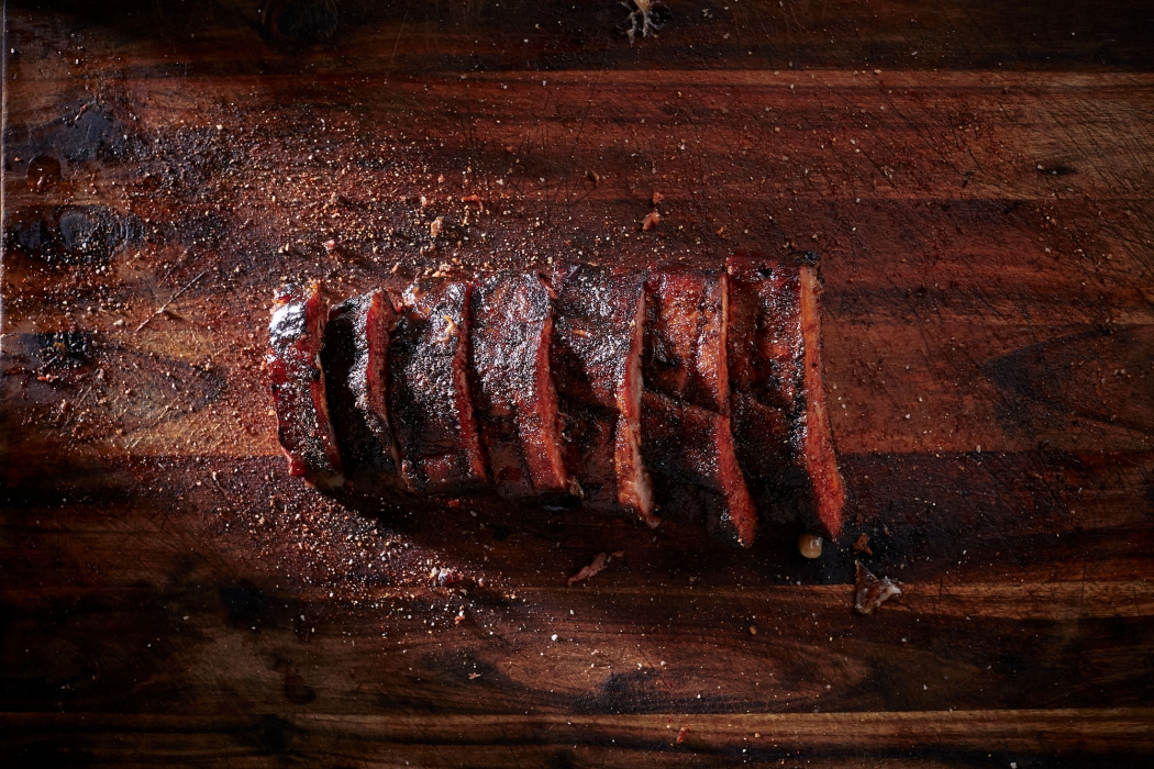A beautiful rack of ribs sliced on a cutting board - food photography