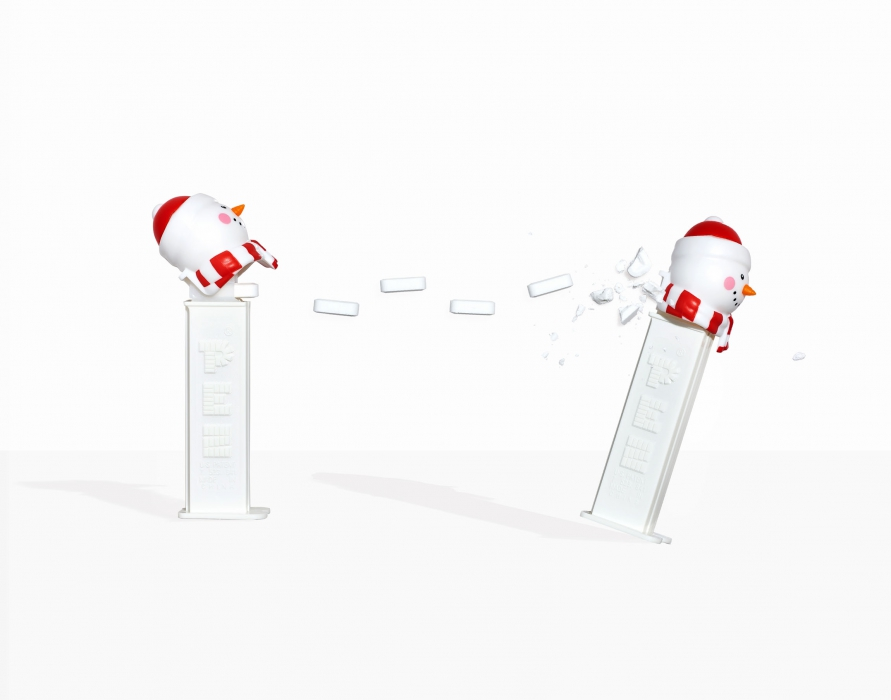 A pez snowman throwing white pez at another pez snowman - food candy photography