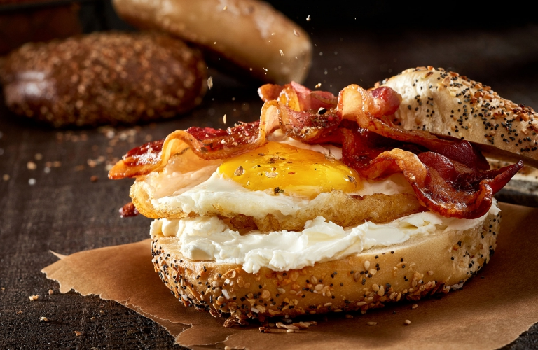 A toasted everything bagel with cream cheese egg and back - food photography