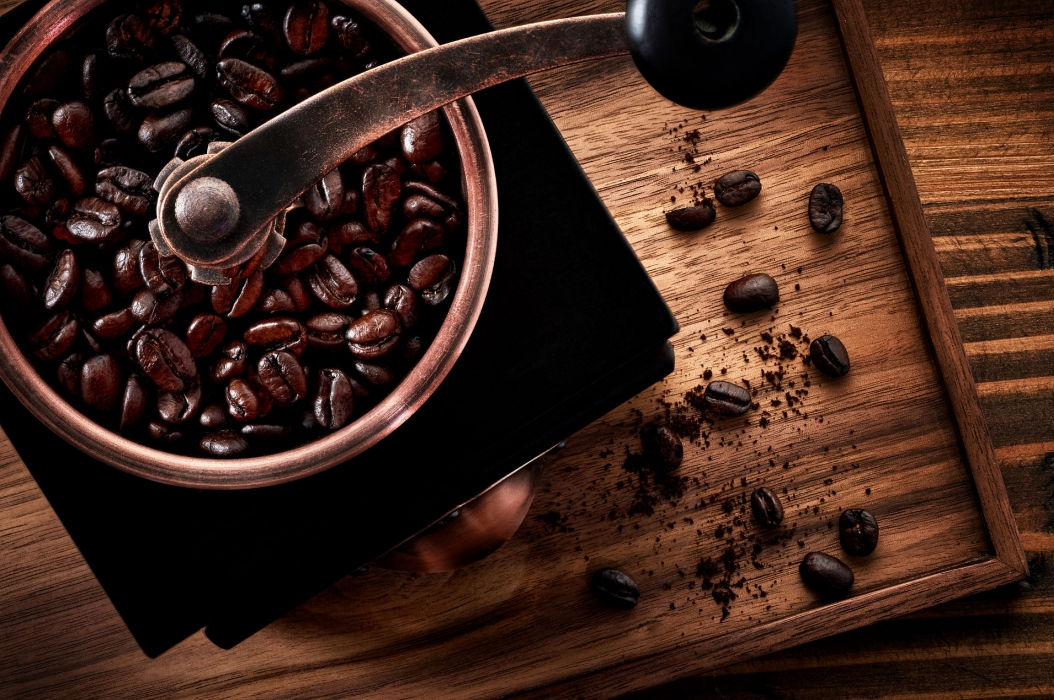 A hand crank coffee grinder and coffee beans - food drink photography