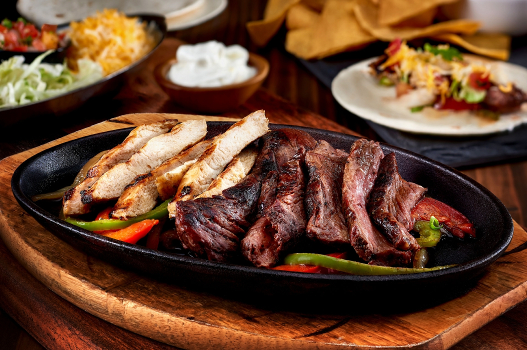 A plate of seared fajitas steak and chicken - food photography