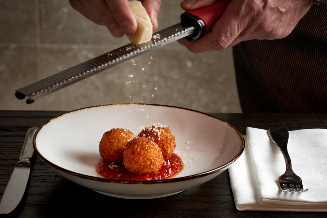Three fine fried cheese balls with shaved cheese - food photography