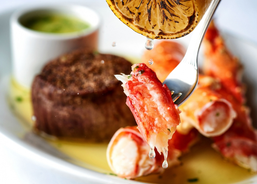 A beautiful shot of crab legs with dripping lemon - food photography