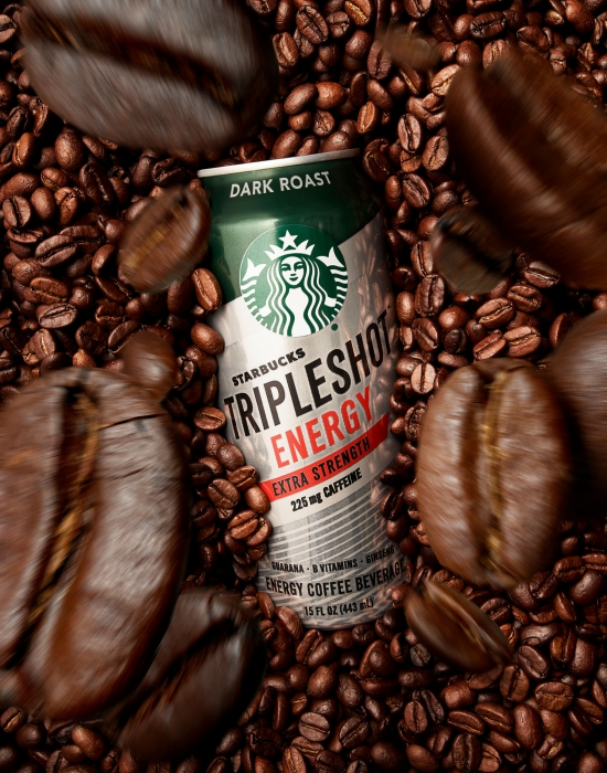 A Starbucks triple shot energy drink surrounded by falling coffee beans - Drink photography
