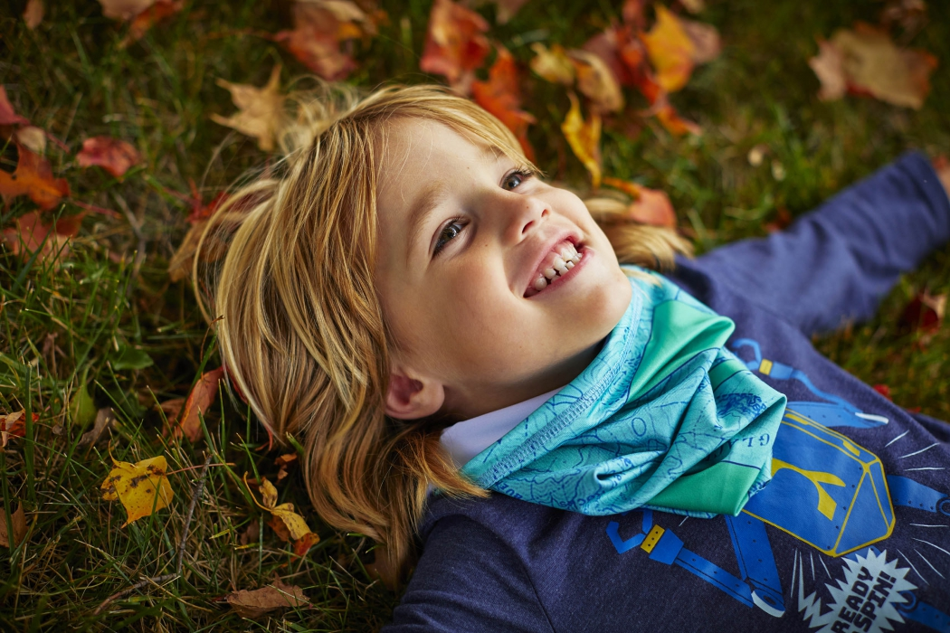 A young boy laying in grass and leaves - lifestyle photography